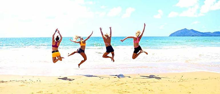 Fire jenter som hopper i vannkanten. Foto.