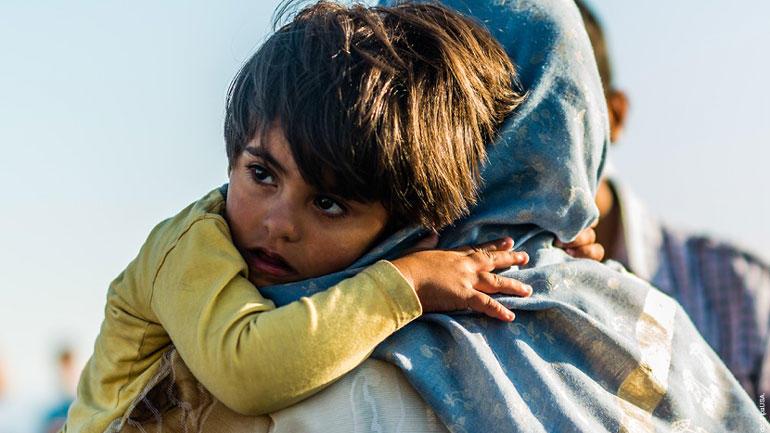 Flyktningemor med barn på skulderen.