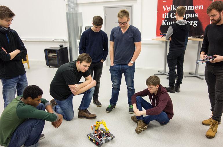 Maskiningeniør-student Lars Berg viser hvordan egen-konstruert mikro-kontroller kan brukes til fjernstyring av robot.  Foto
