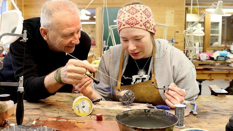 Professor Arne Magnus Johnsrød veileder folkekunststudent Sunna-Inga Gaup Aamot på metallverkstaden. Foto