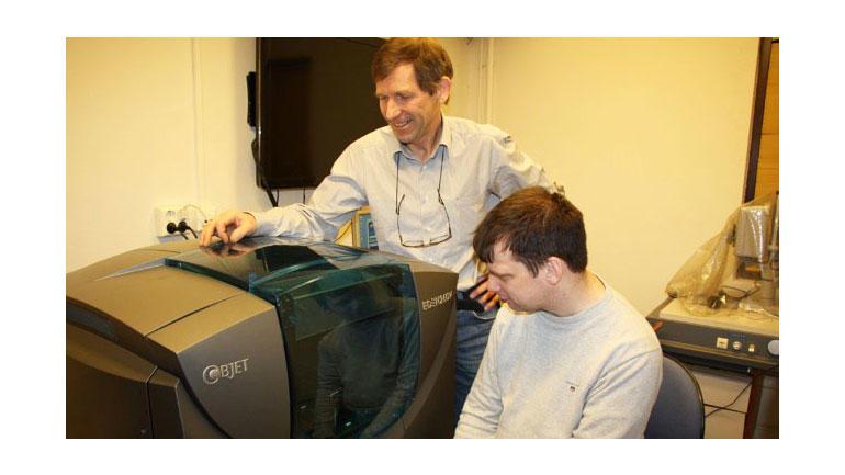HSNs Ole Melteig og oppfinnar Jens Arne Gill Dolmen ventar spente ved 3D-printaren for å sjå den nye prototypen som kjem ut. Foto: Anne Lognvik / NRK.
