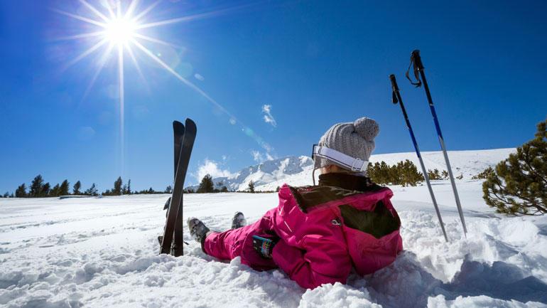 Bilde av jente med ski og staver i solskinn.