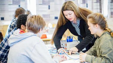 Foto av en underviser og elever i en realfaglig læringssituasjon
