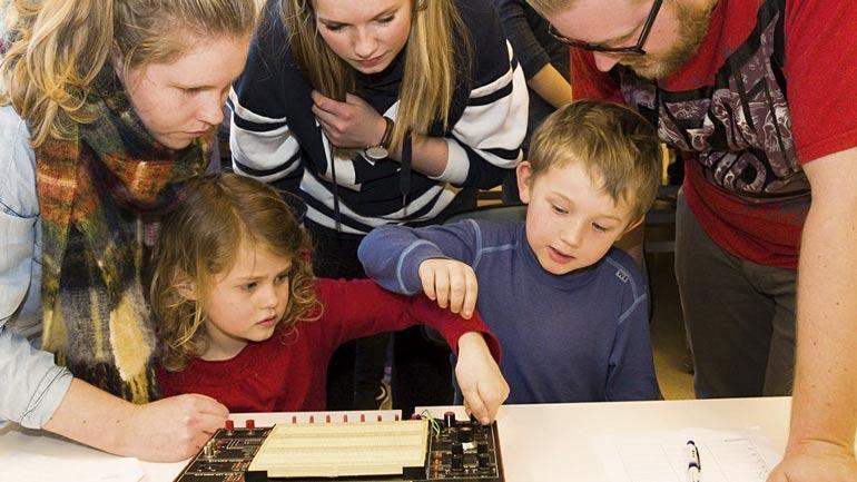 Foto av barn som jobber med en elektrisk tavle mens barnehagelærere bistår.