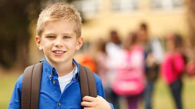 Gutt med sekk foran skole. Foto