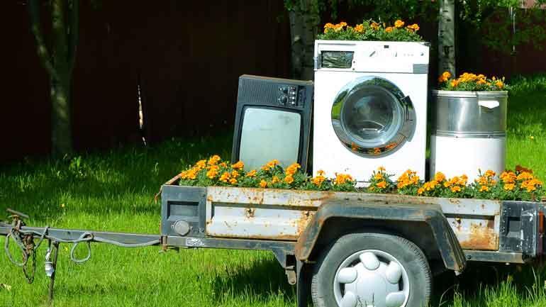 En gammel tilhenger som innholder gule blomster og gammel elektronikk.