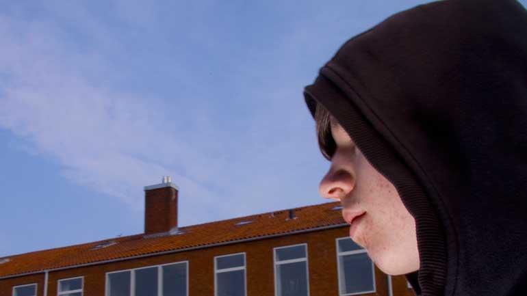 En ung gutt skjult av hettegenseren