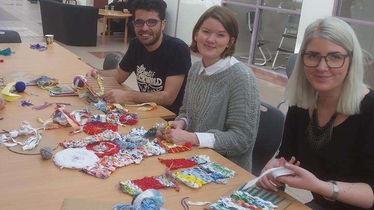Foto av beboere og studenter som samarbeider om et veveprosjekt.