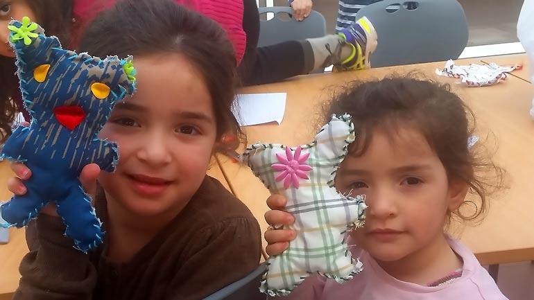 To barn ved Raumyr flyktningmottak viser stolt fram dukkene de lagde sammen med HSN-studentene
