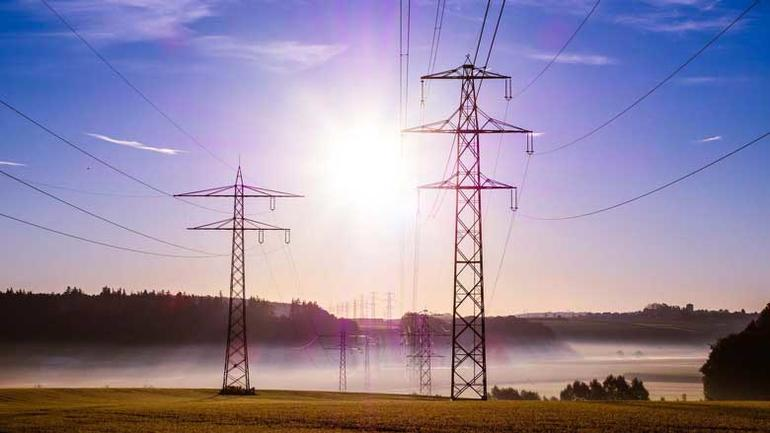 Bildet viser strømmaster utover et jorde.