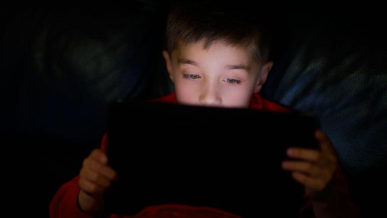 Gutt leser fra iPad.  Foto. iStock.com/fiorigianluigi