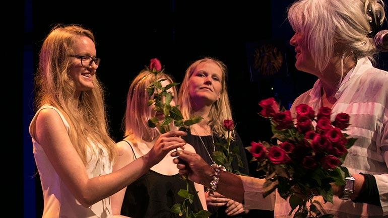 Avgangsstudenter mottar roser. Foto