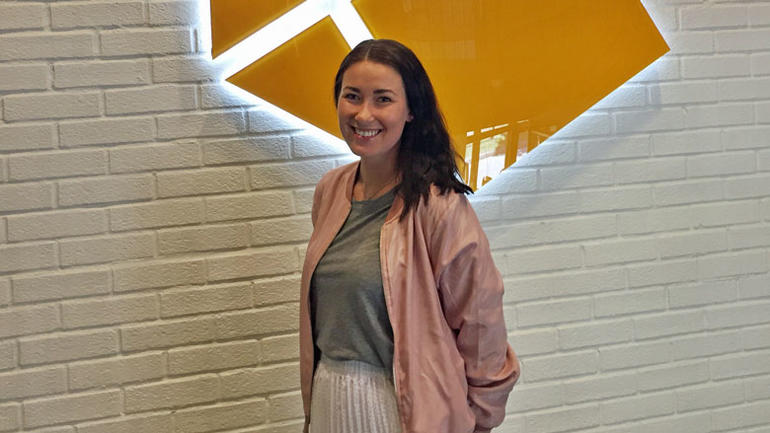 Bilde av Sandra Lindhjem foran Komplett-logo