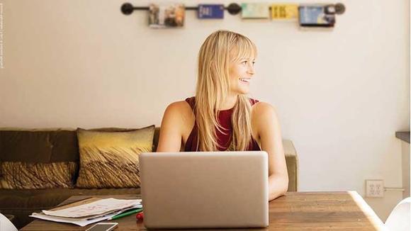 Dame sitter foran pc og studerer nettstudier ved Høgskolen i Sørøst-Norge. Foto.