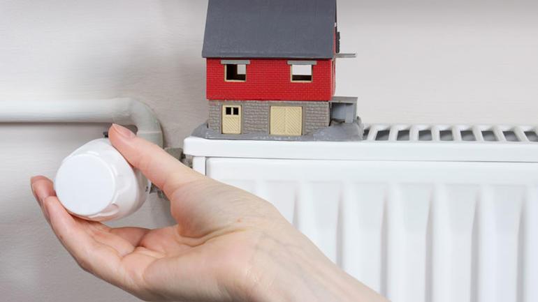Illustrasjonsbilde - radiator, hånd, termostat, hus.  iStock/morisfoto