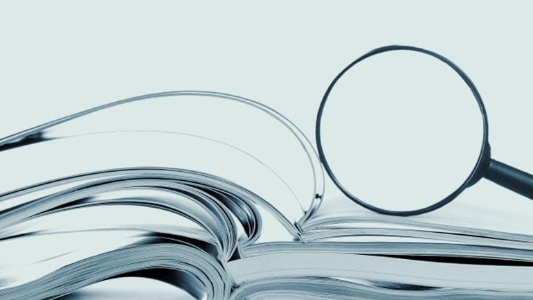 Illustrasjonsbilde. Bok og forstørrelsesglass