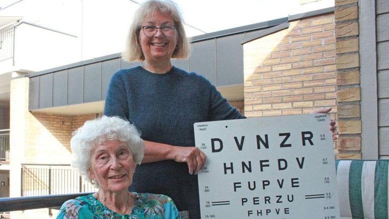 Hjemme hos Inger Lund (89) viser Haanes hvor enkelt en slik synstest kan gjøres. Lund synes hun ser ganske bra, men klarer ikke å se de nederste bokstavene på plakaten fra andre kanten av stua. Foto