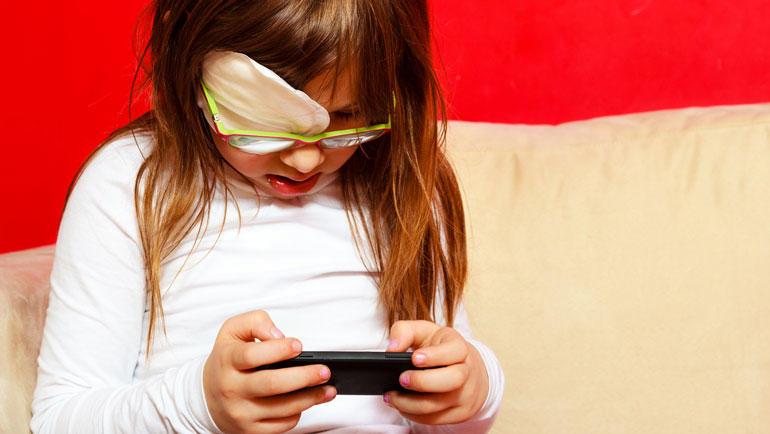 Svaksynt barn med telefon. Foto: iStock/Voyagerix