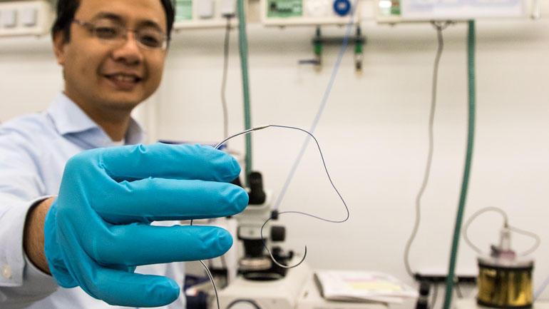 Forsker holder fram mikrosensoren. Foto