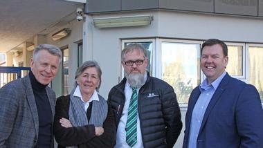 Fire personer samlet foran inngangen til Herøya Industripark.