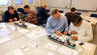Studenter og ansatte jobber med lego-logistikk. Foto