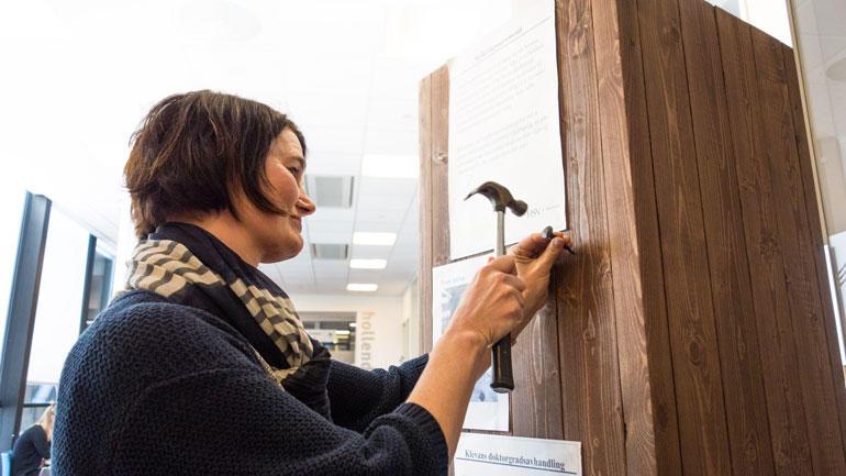 Trude Klevan spikret den ferske doktorgradsavhandlingen sin i personorientert helsearbeid på veggen til høyskolebiblioteket i Drammen.  Foto