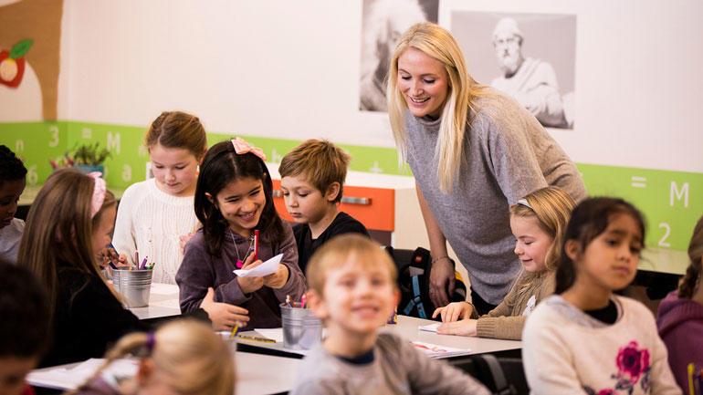 Kvinnelig lærer kommuniserer med en gruppe sittende elever.
