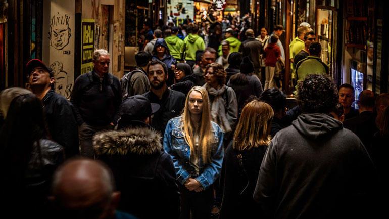 Kvinne alene i folkemengde.