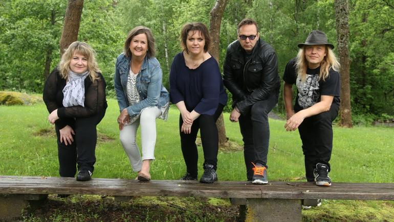 Tre damer og to menn poserer i skogen