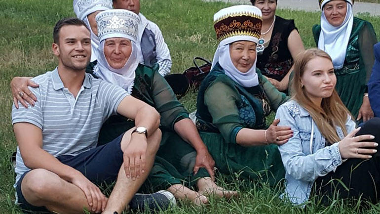 Two students sitting together with the local ladies.