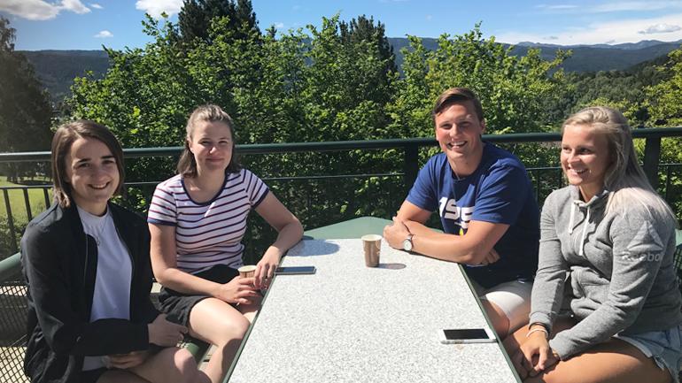 Fire studenter sitter rundt et bord ute i sommersola.