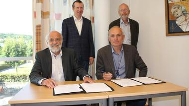 Rektor Petter Aasen (t.h.) og konserndirektør i Skagerak Energi Rune Laurantsen underskriver avtalen. Instituttleder Svein Thore Hagen og FoUi-ekspert Finn Werner Bekken i bakgrunn.