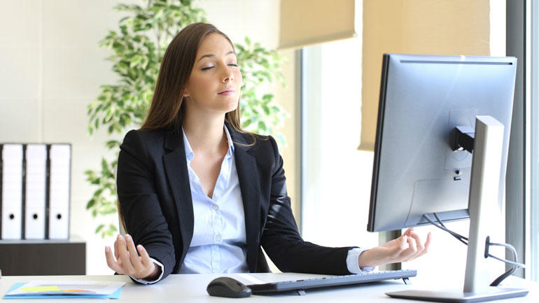 Kvinne mediterer på jobb. foto: iStock/Antonio Guillem
