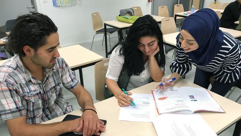 To personer sitter ved en pult og får undervisning av en lærer.