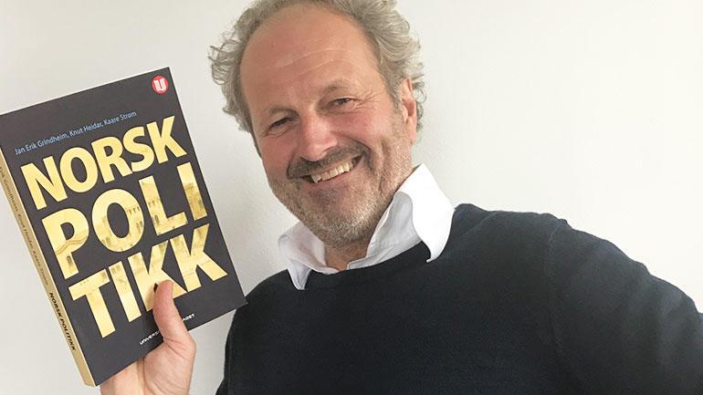 Jan Erik Grindheim med bok. Foto
