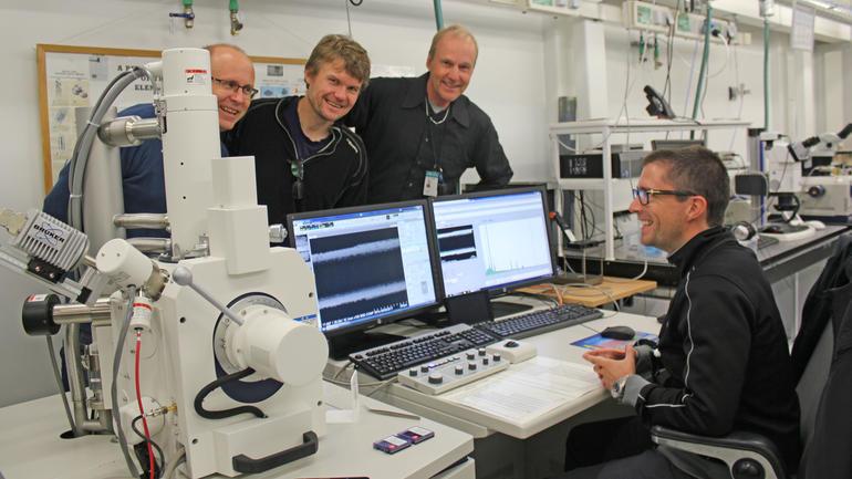 HSN-nøkkelpersoner samlet rundt elektronmikroskopet.