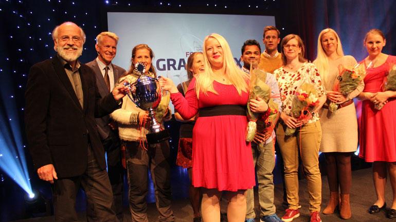 Vinner Karina Rose Mahan tar imot pokal fra rektor Petter Aasen. Resten av deltakerne er også på scenen sammen med prorektor Nils Kristian Bogen.