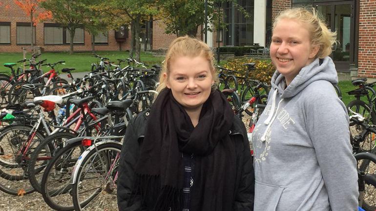 Bilde av de to fornøyde studenter foran sykkelparkering