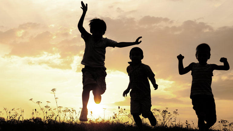 Children playing in sunset. Photo.