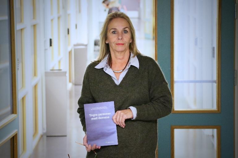 """Aud Johannessen holder opp sin lærebok """"Yngre personer med demens""""."""