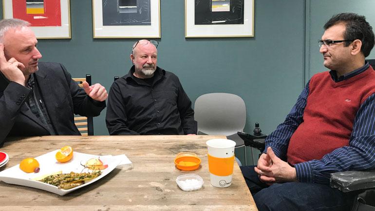 Samlet rundt bordet på kjøkkenet på campus Notodden, dekan Arild Hovland, driftssjef John Hofsrud Roe og Ali. Foto: Jan-Henrik Kulberg