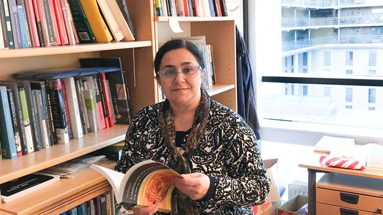 Malahat Nasibova finner bøker om menneskerettigheter i bokhyllen til HSN-mentor Lars Petter Soltvedt. Foto