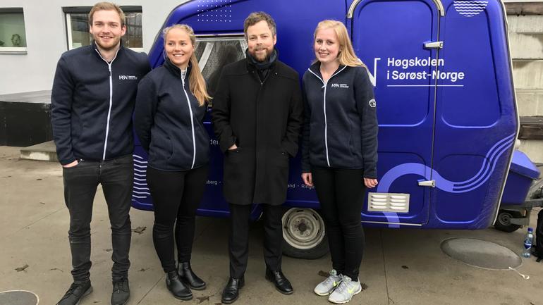 Kunnskapsminsiteren står sammen med tre studenter foran en blå campingvogn