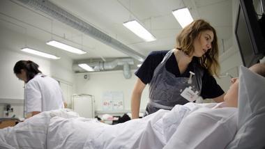Sykepleierstudentene foran sykeseng. foto.