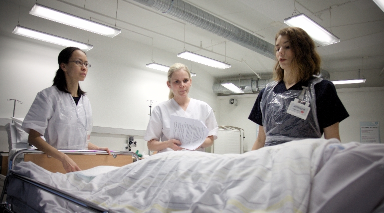 Sykepleierstudenter foran sykeseng på Vitensenteret i Drammen. foto