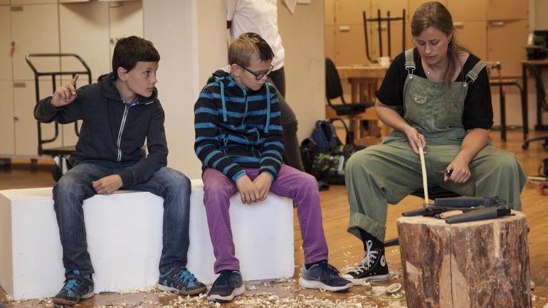 Lærer underviser elever i kunst og håndverk. Foto.