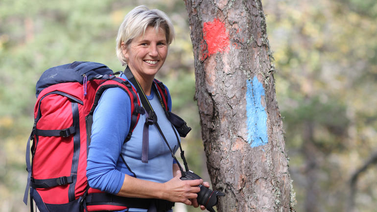 Smilende dame står ved et tre med sekk på ryggen og camera i hånden.