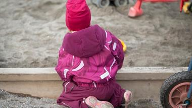 Barn i sandkasse. Foto.