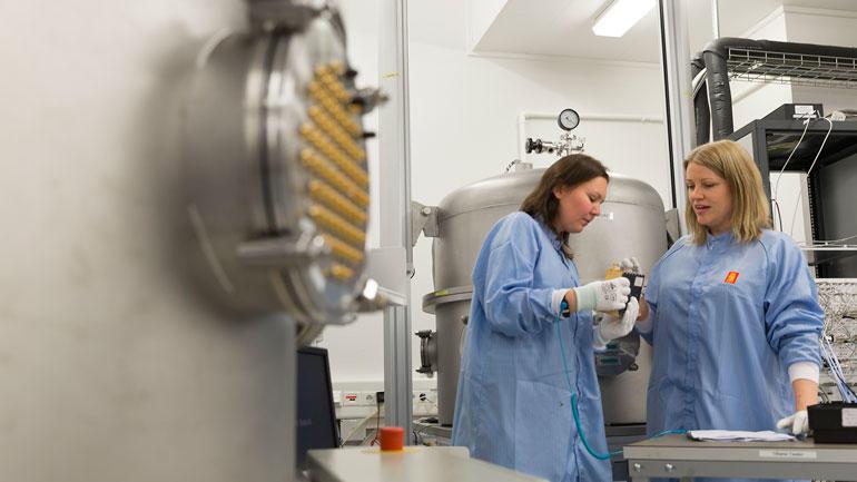 Lisa-Marie Fehn Johansen sammen med kollega Hege Holst-Pedersen som også er test-ingeniør. Her står de inne på test-laben ved vacuum kammerne og testutstyret.
