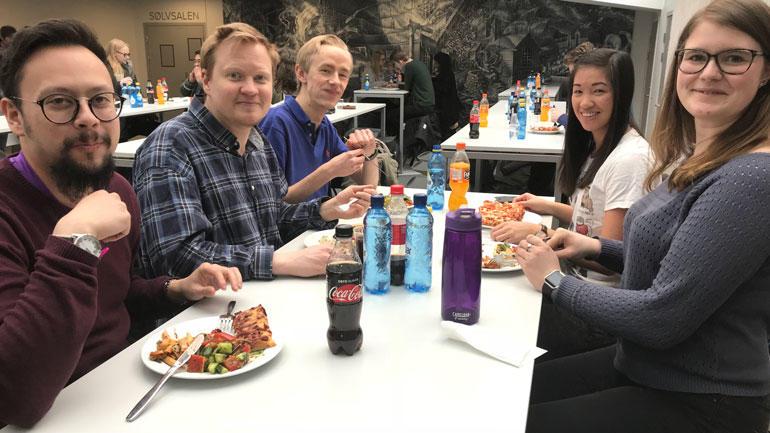Optometristudenter spiser pizza rundt et bord. Foto